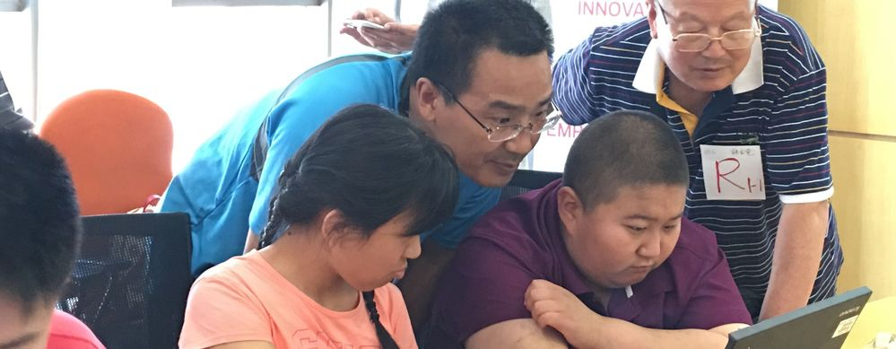 The Beijing team developed an accessible, engaging computer science-focused workshop for students of RARL. Here, two students share the programming experience with Xing Hui, Veritas staff, and the grandfather of one student.